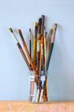 Verfborstels in kruik over houten aqua blauwe achtergrond Stock Foto