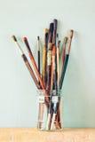 Verfborstels in kruik over houten aqua blauwe achtergrond Stock Afbeelding