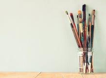 Verfborstels in kruik over houten aqua blauwe achtergrond Stock Fotografie