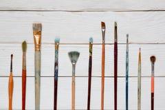 Verfborstels op een witte houten achtergrond, hoogste mening Royalty-vrije Stock Fotografie