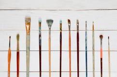Verfborstels op een witte houten achtergrond, hoogste mening Royalty-vrije Stock Afbeeldingen