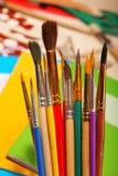 Verfborstels op oefenboekachtergrond Stock Afbeeldingen