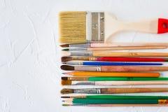 Verfborstels van verschillende grootte en potloden op witte textuurachtergrond Kunst en onderwijsvoorwerp stock afbeelding
