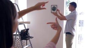 Verfraai binnenlands, hangt de aantrekkelijke kerel beeld terwijl de vrouw kader met vinger maakt en beslist over decoratie bij n stock videobeelden