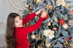 Verfraai Kerstmisboom het gelukkige meisje viert de wintervakantie Gelukkig Nieuwjaar De tijd van Kerstmis Leuk weinig kind royalty-vrije stock afbeeldingen