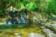 Verfraai van middelgrote waterval rond stenen en bos bij het Nationale Park van Khao Yai stock fotografie