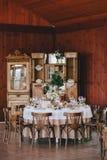 Verfraaide huwelijkslijst in rustieke stijl voor diner met witte en beige tafelkleden, wijnglazen met bloemen en royalty-vrije stock fotografie