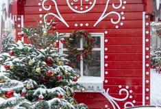 Verfraaide Kerstboom op de achtergrond van een rood fairytalehuis royalty-vrije stock afbeelding