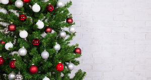 Verfraaide Kerstmisboom met kleurrijke ballen over witte baksteen wa Royalty-vrije Stock Fotografie