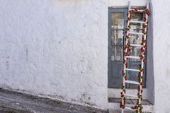 Verfraaide ladder met groene en rode bloemen op uitstekend oud wit stock afbeeldingen