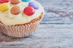 Verfraaide muffin met witte chocolade op houten oppervlakte stock afbeelding