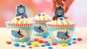 Verfraaiend de partij van de kinderen` s verjaardag als thema gehad Thomas the Tank Engine cupcakes Stock Afbeelding