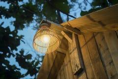 Verfraaiend lantaarn het hangen op houten die bar, a-vertroebelde de lamp van bamboe wordt gemaakt, boom en blauwe hemel op achte Royalty-vrije Stock Afbeeldingen