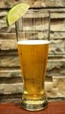 Verfrissend bier met kalk, baksteenachtergrond Royalty-vrije Stock Foto