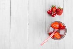 Verfrissend water van rode bessen in een glas op houten lijst Eigengemaakte smakelijke en gezonde dranken stock fotografie