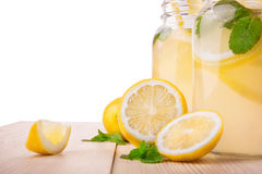 Verfrissende en smakelijke de zomerdranken met rijpe, sappige en verse citroenen, heldergroene die munt en mijnwerker, op een wit Royalty-vrije Stock Foto's