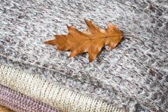 Verfrommelde grijze gebreide die kleren in een stapel worden gevouwen Textuur voor achtergrond of illustraties stock afbeeldingen