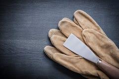 Verfschraper en beschermende handschoenen op houten raad Stock Afbeelding