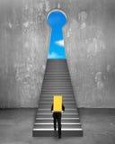 Verga d'oro di trasporto dell'uomo d'affari sulle scale per chiudere a chiave la porta di forma Fotografia Stock Libera da Diritti