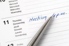 Vergadering die nota in kalender eraan herinnert Stock Foto's