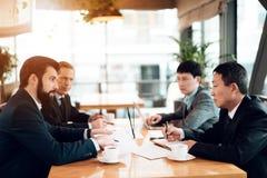 Vergadering met Chinese zakenlieden in restaurant Zij bespreken punt in documenten stock afbeelding