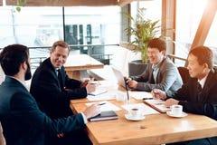 Vergadering met Chinese zakenlieden in restaurant Zij zitten achter lijst stock afbeeldingen