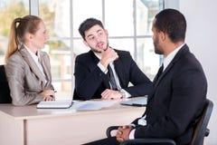 Vergadering met een cliënt Drie het succesvolle bedrijfsmensen zitten stock foto