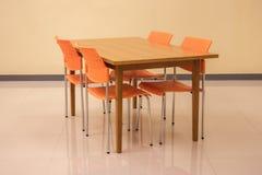 Vergaderingslijst en oranje stoelen Stock Fotografie