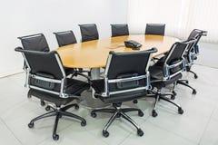 Vergaderingslijst en zwarte haren in vergaderzaal Stock Fotografie