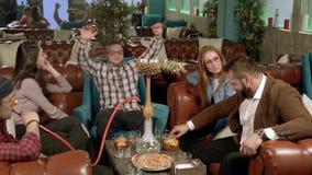 Vergaderingsvrienden in de koffie Jongeren die waterpijp roken en in een koffie rusten stock videobeelden