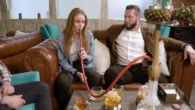 Vergaderingsvrienden Jongeren die waterpijp roken en in een koffie rusten stock video