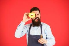 Vergeet over dieet Bedrieg maaltijd Verglaasde doughnut van de Hipster de gebaarde bakker greep op rode achtergrond Koffie en bak stock afbeeldingen