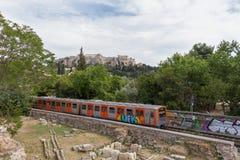 Övergående drev till och med den forntida marknadsplatsen för Aten med akropolen i Arkivbilder