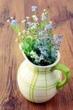Vergessen Sie mich nicht Blume auf antiker Milchdose stockfotografie