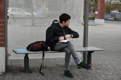 Vergessene Schulhausarbeit, Junge überprüft die Zeit bis den Bus ankommt Stockbilder