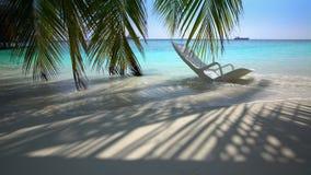 Vergessener Strandstuhl auf dem tropischen Strand in den Meereswogen