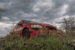 Vergessenes irgendwo rotes Auto vernachlässigtes und gebrochenes Auto Lizenzfreie Stockbilder