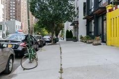 Vergessenes und gebrochenes Fahrrad wird zu einem Pfosten am Rand von t befestigt Lizenzfreies Stockfoto