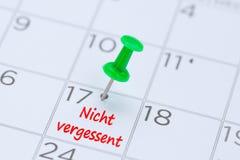 Vergessent Nicht geschreven op een kalender met een groene duwspeld aan Royalty-vrije Stock Afbeeldingen
