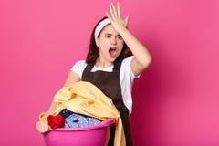 Vergessliche Frau hält Hand auf Stirn, sich erinnert, dass sie vergaß, das Waschpulver zu kaufen, gekleidet im weißen zufälligen  lizenzfreie stockfotografie