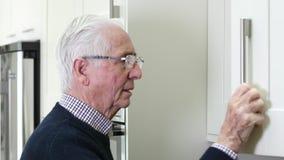 Vergesslicher älterer Mann mit der Demenz, die zu Hause im Schrank schaut stock video footage
