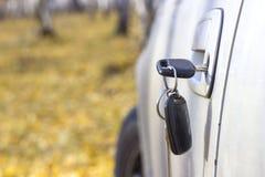 Vergeten autosleutels in de deur, een achtergrond van een onscherp de herfstbos met een bokeheffect stock fotografie