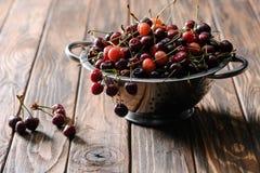 vergiet met verse zoete gezonde kersen op plattelander stock afbeeldingen