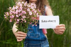 Vergiffenis - vrouw met woord en boeket van roze bloemen stock afbeeldingen