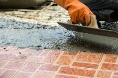 Vergipsender Arbeitszement mit Kelle für neuen Boden der Gestalt für Reno Stockbild