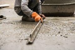 Vergipsender Arbeitszement mit Kelle für neuen Boden der Gestalt für Reno Stockfoto