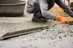 Vergipsender Arbeitszement mit Kelle für neuen Boden der Gestalt für Reno Stockbilder