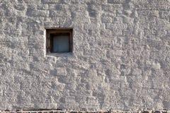 Vergipste Backsteinmauer und kleines Fenster Stockbilder