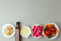 Vergiste groenten op plaat op grijze achtergrond: zuurkool, ingelegde kool met bieten, ingelegde komkommers, wortelen en royalty-vrije stock foto's