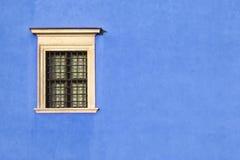 Vergittern Sie Fenster auf einer blauen Wand mit Kratzern Stockfotografie